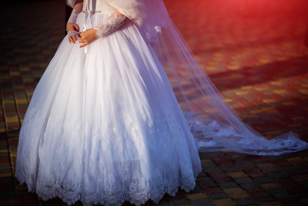 Abito da sposa bianco bellissimo con lacci di una giovane sposa sul marciapiede
