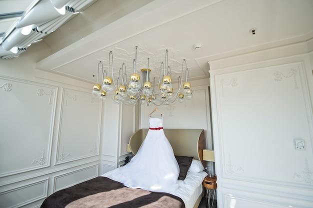 Abito da sposa bianco della sposa appesa al lampadario nella camera d'albergo