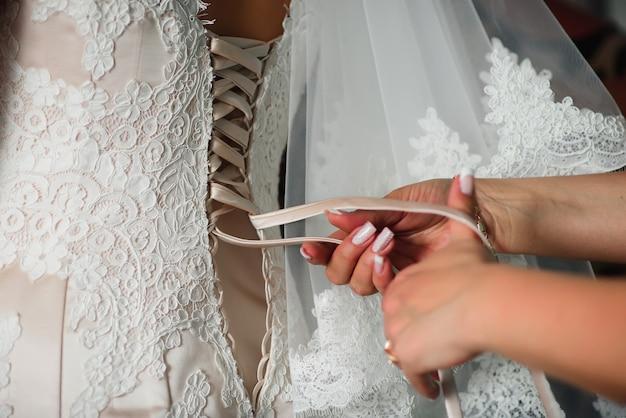 Abito da sposa bianco per allacciare le mani della damigella d'onore