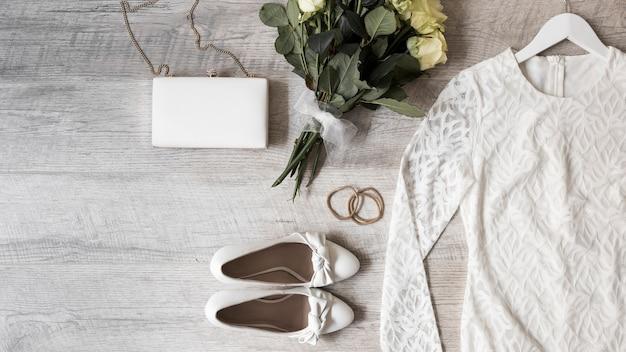 Abito da sposa; bouquet di fiori; scarpe da sera; frizione e fermagli per capelli su fondo in legno