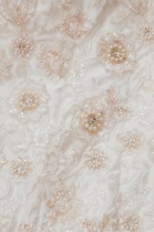 Abito da sposa con accessori decorativi in seta color crema, pizzi e perle
