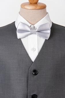 Abito grigio da uomo bello con camicia e papillon bianco.