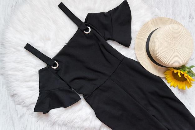 Abito nero su pelliccia bianca, cappello e girasoli.