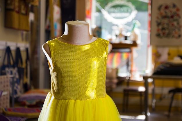 Abito per bambini giallo con scintillii su manichino. piccolo vestito giallo in studio.