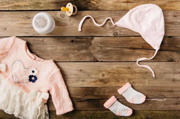 Abito rosa da bambino con copricapo; un paio di calzini; bottiglia di latte e ciuccio sul tavolo di legno
