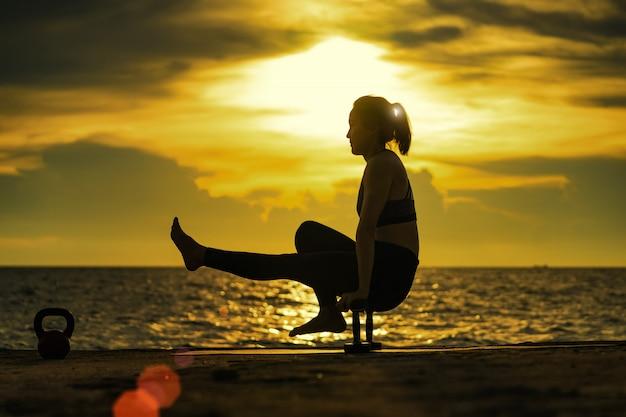 Abstrac. yoga della siluetta. ritratto di giovane donna che pratica yoga al mare. rilassarsi al mare. meditazione