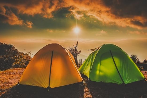 Accampandosi e tende su terra alta con il tramonto dell'alba sopra la nuvola della nebbia a doi ang khang chiangmai, tailandia