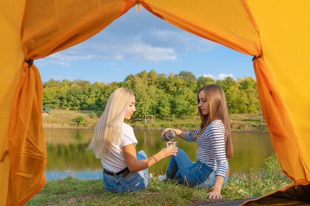Accampandosi sulla riva del lago al tramonto, vista dall'interno della tenda di campeggio. due belle ragazze godono della natura e bevono tè caldo davanti alla tenda