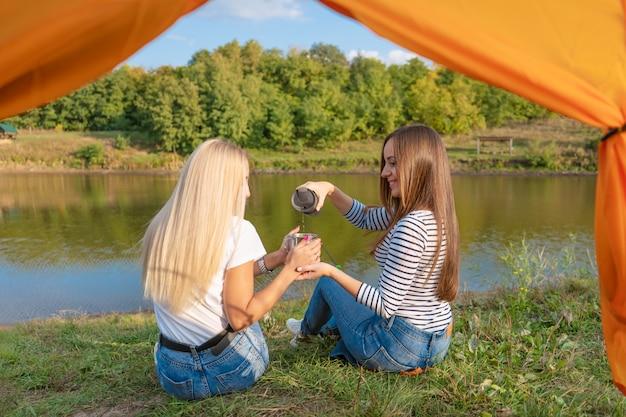 Accampandosi sulla riva del lago al tramonto, vista dall'interno della tenda di campeggio. due belle ragazze si godono la natura e bevono tè caldo davanti alla tenda