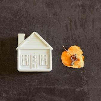 Accanto a una piccola casa di giocattoli c'è una chiave su una foglia autunnale gialla.