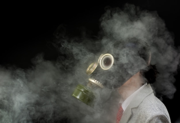 Accanto all'uomo in una maschera antigas con molti fumi, disastro ambientale