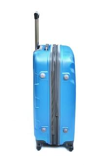 Accanto alla valigia blu isolata su bianco