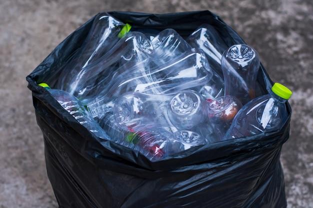 Accatasti le bottiglie di plastica riciclabili in borsa di rifiuti