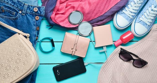 Accessori alla moda femminile, scarpe, vestiti e gadget moderni su un fondo di legno blu. jeans, borsa, scarpe da ginnastica, smartphone, braccialetto intelligente, power bank, cosmetici, occhiali da sole, sciarpa. vista dall'alto.