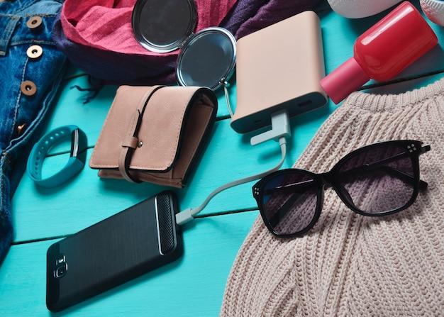 Accessori alla moda femminile, scarpe, vestiti e gadget moderni su un fondo di legno blu. jeans, borsa, scarpe da ginnastica, smartphone, braccialetto intelligente, power bank, cosmetici, occhiali da sole, sciarpa.