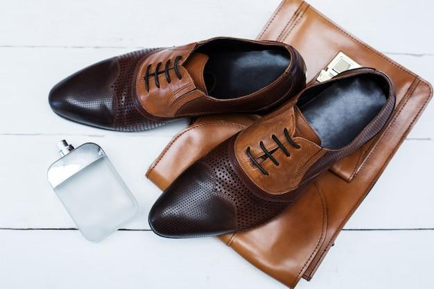 Accessori alla moda. scarpe maschili con borsetta e profumo