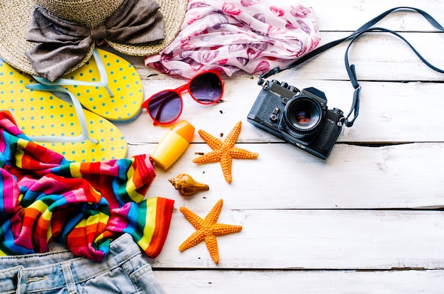 Accessori costume con viaggio per l'estate sul pavimento di legno