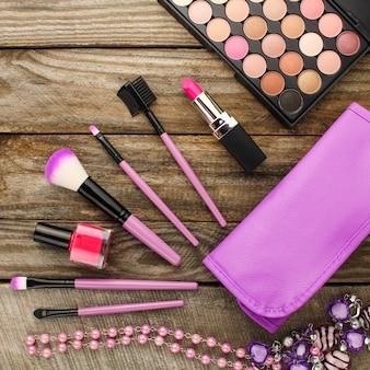 Accessori da donna: borsa per cosmetici, pennelli per trucco, collana, smalto per unghie, rossetto. vista dall'alto.