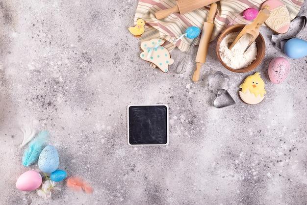 Accessori da forno su fondo in pietra con farina, uova e biscotti lustrati pasquali.