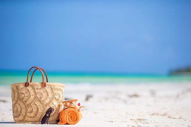 Accessori da spiaggia - aereo giocattolo, borsa di paglia, asciugamano arancione e bicchieri di vetro sulla spiaggia