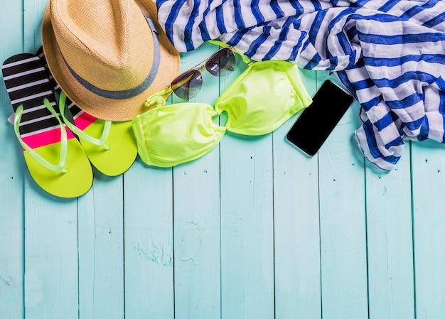 Accessori da spiaggia con costume da bagno giallo, occhiali da sole e infradito
