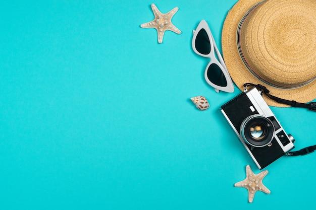 Accessori da spiaggia retro macchina da presa, occhiali da sole, cappello da spiaggia di stelle marine e conchiglia su fondo blu per le vacanze estive e le vacanze