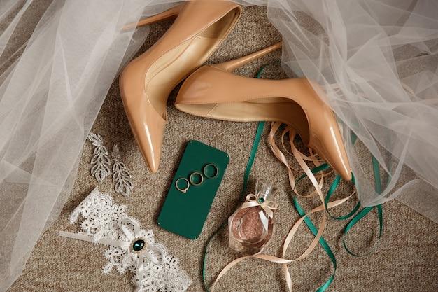 Accessori da sposa per la sposa. scarpe da sposa su tacchi alti, giarrettiera da sposa, bottiglia di profumo e tre anelli