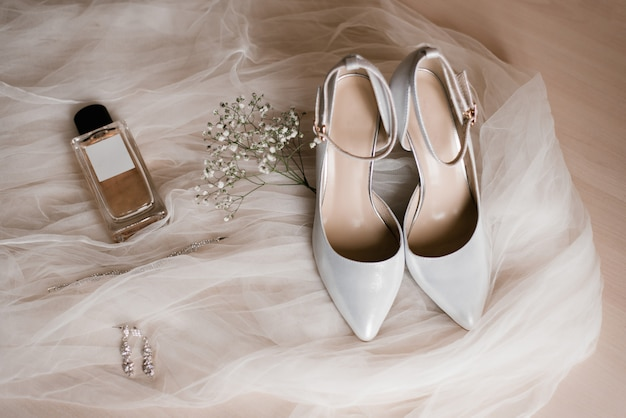 Accessori da sposa: scarpe, eau de toilette o profumo, orecchini e un rametto di fiori di gypsophila su tulle