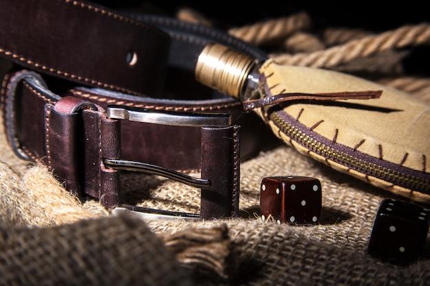 Accessori da uomo con cintura in pelle marrone, occhiali da sole, orologio, pipa da fumo e bottiglia con profumo