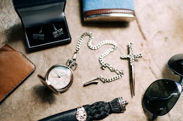 Accessori da uomo: occhiali, coltello, fiaschetta, orologio con catena, gemelli, portafoglio, croce su una trama di pietra