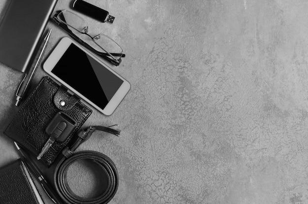 Accessori da uomo su uno sfondo di cemento nero. il concetto di uomo moderno di successo. copia spazio