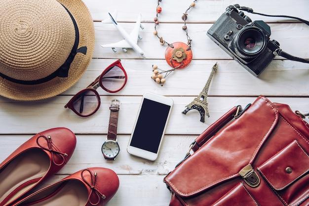 Accessori da viaggio e costume sul pavimento di legno