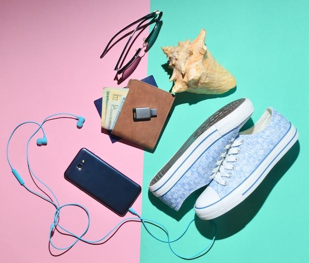 Accessori da viaggio per donna. scarpe da ginnastica, borsa, passaporto, occhiali da sole, unità flash, smartphone, cuffie. vista dall'alto. disteso.