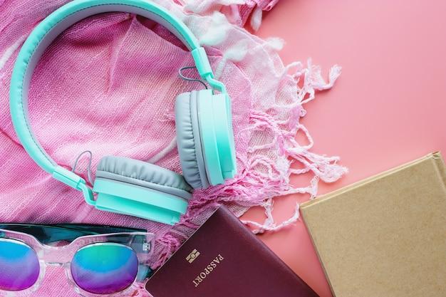 Accessori da viaggio su sfondo rosa