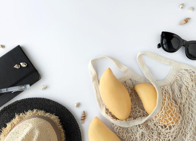 Accessori del viaggiatore di vista superiore laici piatti, frutta, cappello di paglia su fondo bianco con spazio vuoto per testo
