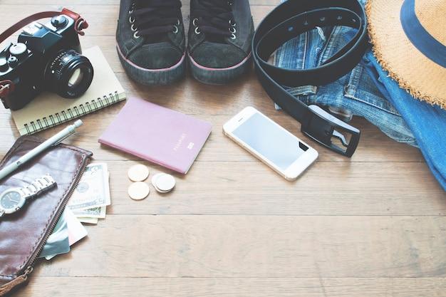 Accessori del viaggiatore, elementi essenziali di vacanza di giovane con passaporto, macchina fotografica, dispositivo mobile e borsa su sfondo di legno con copia spazio