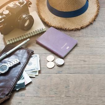 Accessori del viaggiatore, elementi essenziali di vacanza di giovane con passaporto, macchina fotografica e borsa su sfondo di legno con spazio di copia