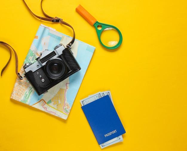 Accessori del viaggiatore, retro macchina fotografica su colore giallo. lay piatto