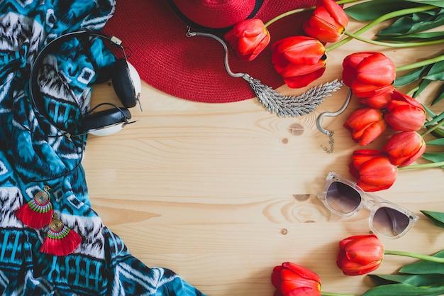 Accessori della donna e tulipani rossi sul tavolo
