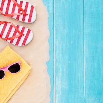 Accessori della spiaggia sulla plancia e sulla sabbia blu - fondo di vacanza estiva