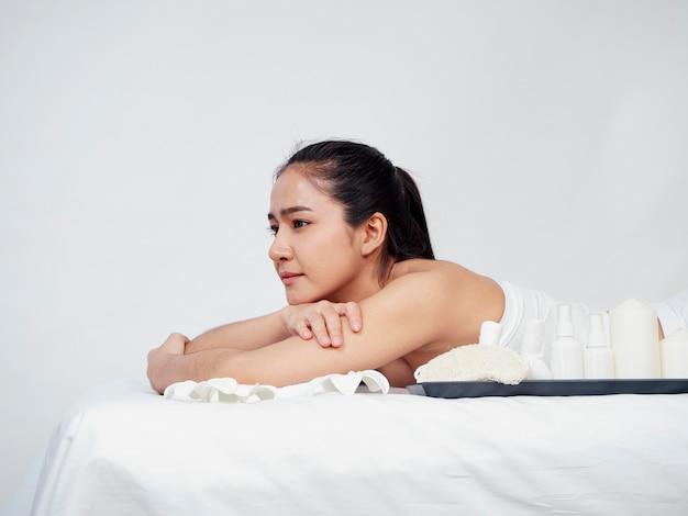 Accessori della stazione termale e della giovane donna sulla tavola di massaggio