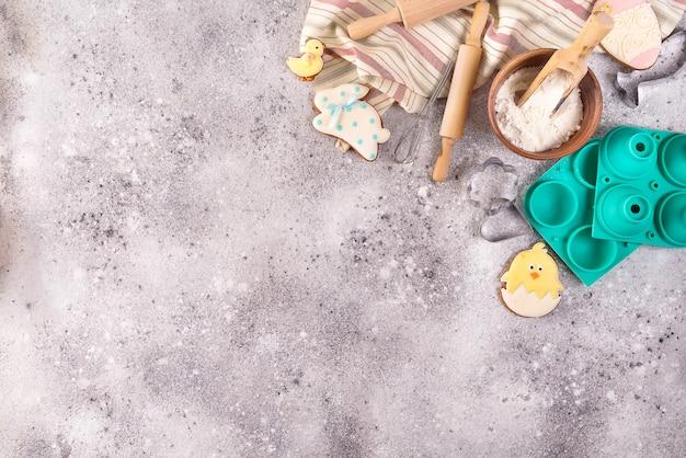 Accessori di cottura su fondo di pietra con farina e biscotti lustrati di pasqua.