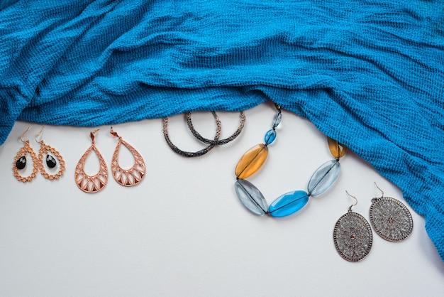 Accessori di moda femminile in stile orientale su bianco orecchini gioielli sciarpa blu