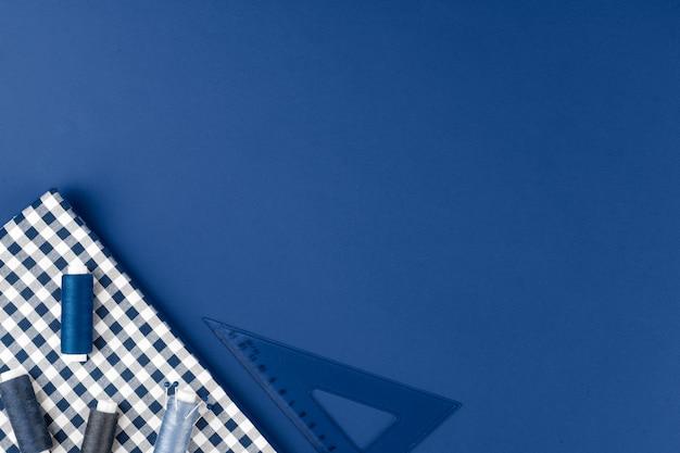 Accessori di tayloring su fondo blu classico, vista dall'alto