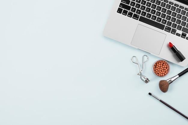 Accessori di trucco e del computer che mettono su fondo leggero