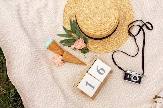Accessori di una ragazza romantica che viaggia. cappello di vimini e fotocamera retrò