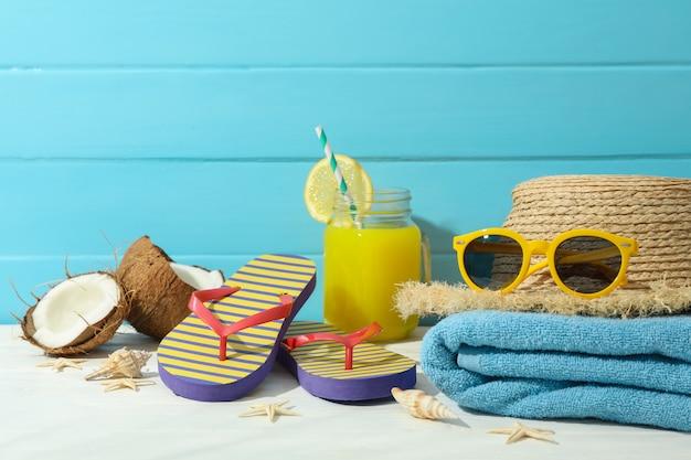 Accessori di vacanze estive sulla tavola bianca contro il fondo di legno di colore, spazio per testo. buone vacanze