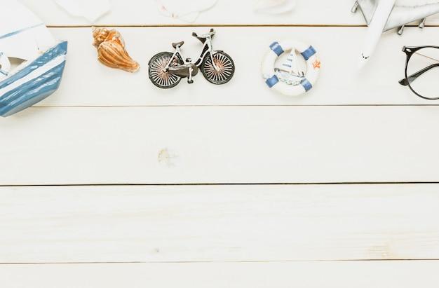 Accessori di vista superiore per viaggiare barca a vela beach.vintage con bicicletta di conchiglia su sfondo in legno.
