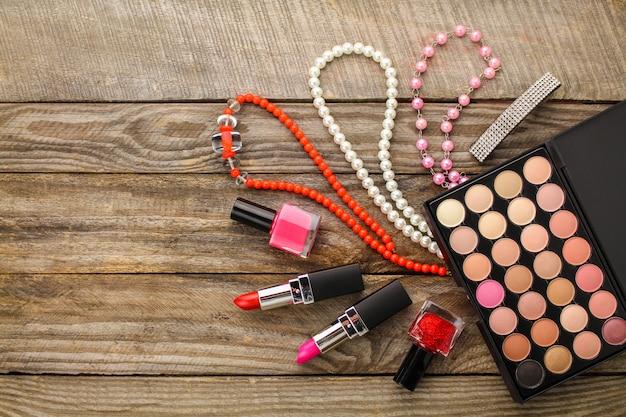 Accessori donna: collana, smalto per unghie, rossetto, fermacapelli, ombretto. vista dall'alto.