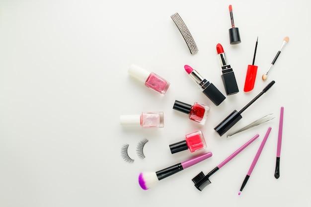 Accessori donna e cosmetici su sfondo bianco.